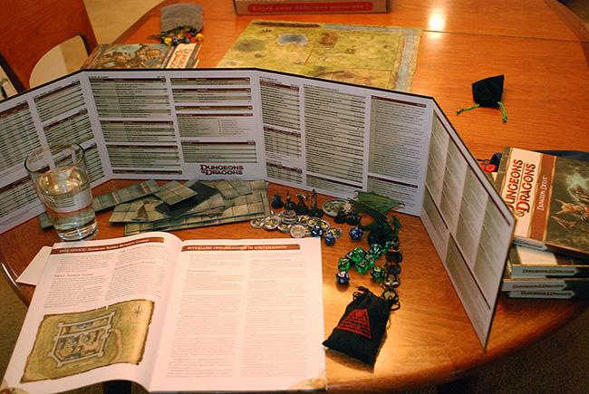 Clásica partida de D&D 4ª Ed. con su mapa y figuras para colocar. Podemos ver también la pantalla del DM, detrás de la cual realiza en secreto sus tiradas y que le sirve de guía rápida sobre las reglas. Estas pantallas son uno de los múltiples productos que se venden con cada nueva edición.